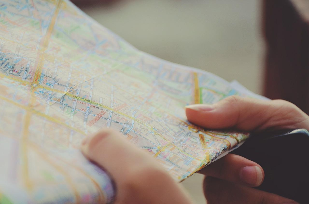 man holding road atlas map